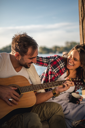 Couple laughing and playing guitar by the river on a sunny day Imagens