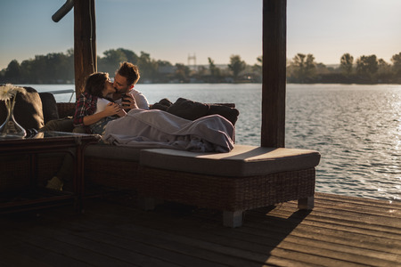 Couple lying under the blanket and kissing by the river ona sunny day Standard-Bild - 118085157