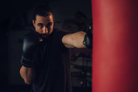Boxer with beard hitting the heavy bag with front jab 写真素材