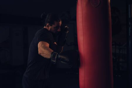 Boxer with beard hitting the heavy bag with right hook