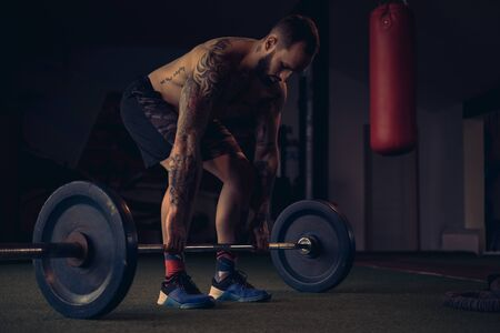 Tattooed male athlete start lifting weight from the floor 写真素材