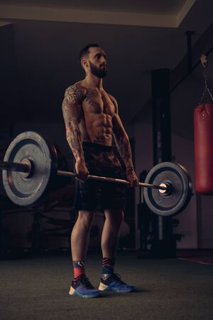 Tattooed male athlete lifting weight from the floor 写真素材