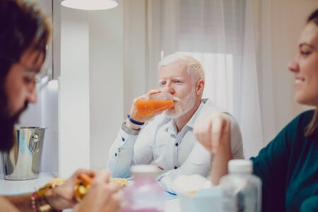 Handsome albino man drinking juice at the dinner with friends Stock Photo