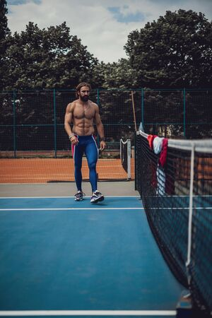 Handsome shirtless man walking on the tennis court