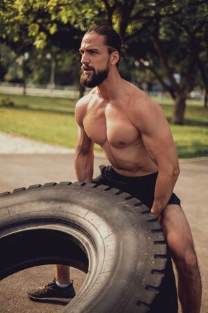 Bearded muscled hipster training with tire in the outdoor gym