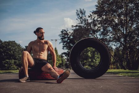 Tired bearded man resting on a tire after workout in the sun
