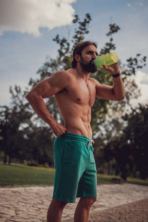 Bearded muscular man drinking water outdoors after workout