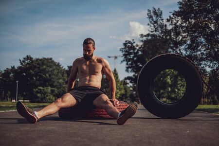 Tired bearded man sitting on a tire after workout in the sun Stock Photo
