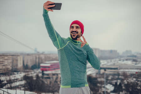Smiling athletic man taking selfie on a cold winter day with cityscape in the background