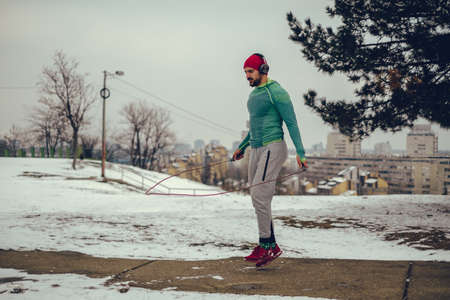 Male athlete jumping rope and listening music on a cold winter day