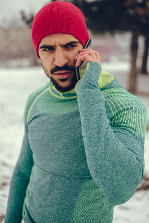 Male athlete talking on the mobile phone outdoor on a cold winter day