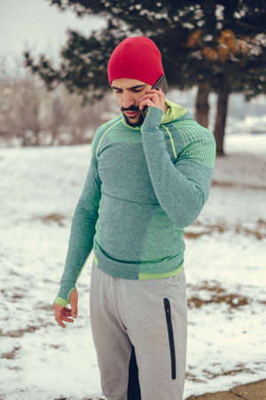 Fit man talking on the mobile phone outside on a snowy winter day