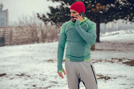 Fit bearded man talking on the mobile phone outside on a cold winter day