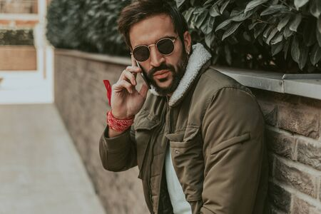 Tough, urban, bearded man talking on the phone in the city