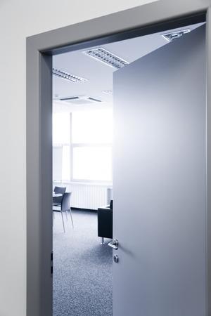 Open deur van het kantoor raam stoelen en tapijt Stockfoto