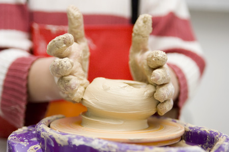 Child hands working on pottery wheel toy Stock Photo