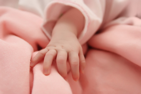 Hand of a sleeping newborn baby - macro - selective focus Stock Photo
