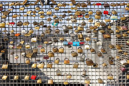 colourful padlocks hanging on fence