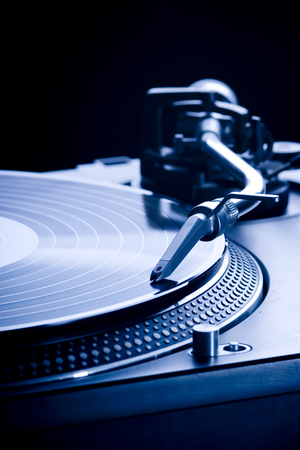 Record player playing LP in dark room, macro picture Stock Photo