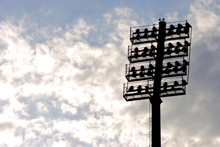 Stadium lights, silhouetted on cloudy background Reklamní fotografie