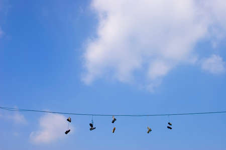 Old shoes hang on wire