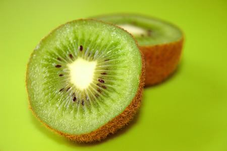 Ripe half kiwi fruit on green background Reklamní fotografie