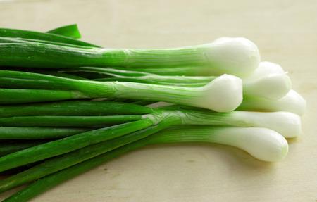 bunch of green spring onions on cutting board, macro Stock Photo - 121562979