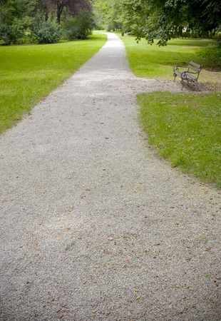 bench in a park, gravel path and grass