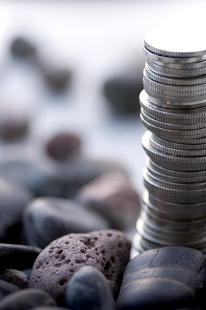 Coin stacks on a white background with stones - macro depth of field Stock Photo