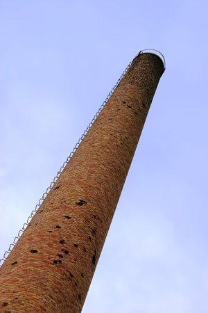 Old weathered tall industrial factory chimney, red grungy brick smokestack perspective