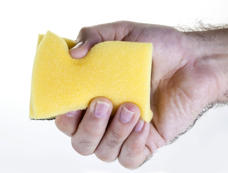 Male hand holding yellow dish washing sponge Stock Photo - 121562708
