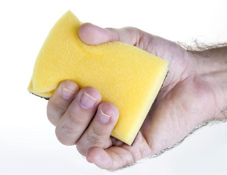 Male hand holding yellow dish washing sponge