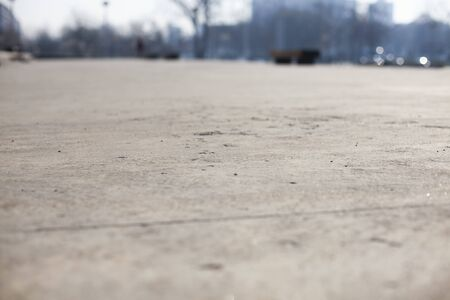 Close perspective of concrete floor, blurry background