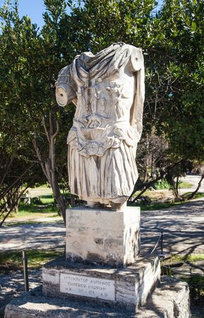 Statue of the torso of Hadrian standing in the ancient Agora of Athens, Greece. Photo shows the tunic depicting Athena standing above a she-wolf feeding Romulus and Remus.