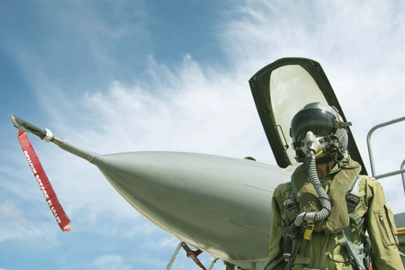 Pilot with military suit and military aircraft