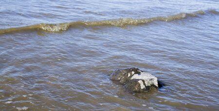 overrun: waves overrun a single stone in the sea