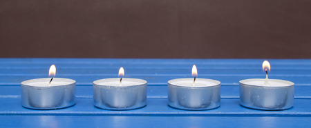 four candles in a row on a table Stock Photo