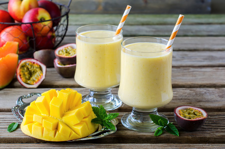 Healthy vitamin tropical mango and passion fruit smoothie with yogurt milkshake two glasses on wooden background