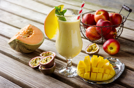 Healthy vitamin tropical mango, melon and passion fruit smoothie with yogurt on old wooden background, milkshake