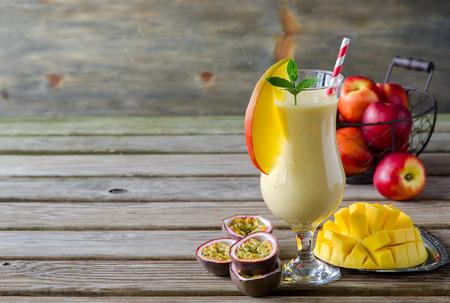 Gezonde vitamine tropische mango en passievruchten smoothie met yoghurt en perziken, milkshake, kopiëren ruimte achtergrond