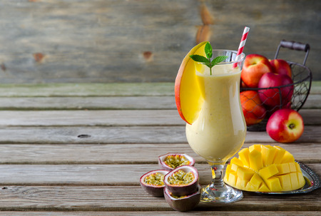 Healthy vitamin tropical mango and passion fruit smoothie with yogurt and peaches, milkshake, copy space background