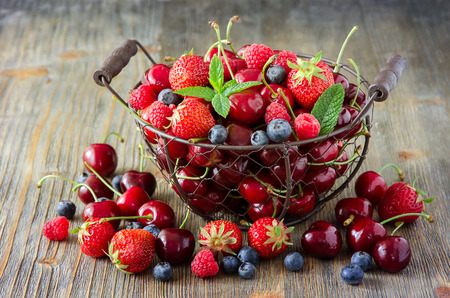 Fresh ripe berries mix, cherries, raspberries, blueberries in vintage basket, summer harvest concept, vitamins, healthy food Archivio Fotografico