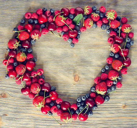Fresh ripe berries, cherries, raspberries, blueberries lots of copy space, wooden background, summer fruits, harvest concept, vitamins food, heart shaped, square toned image