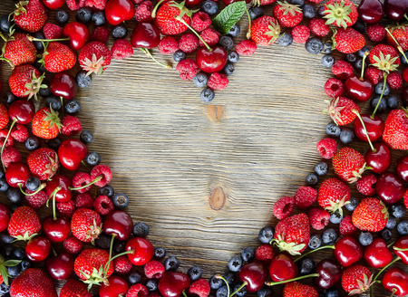Fresh ripe berries, cherries, raspberries, blueberries copy space background, summer fruits, harvest concept, vitamins food, heart shaped