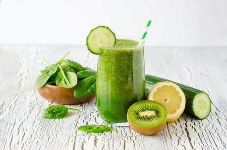 白い木製の背景、ダイエットと健康の概念、ビタミンの新鮮な緑デトックス スムージー