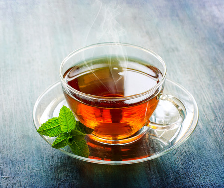 Cup of tea with steam, healthy drink, leaf of mint on dark rustic copy space background Stockfoto