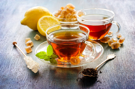 Cup of tea with mint and chrystal sugar on dark rustic background, hot drinks, teatime Standard-Bild
