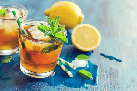 Fresh cold iced tea, lemon and mint cocktail, refreshing summer drink copy space background
