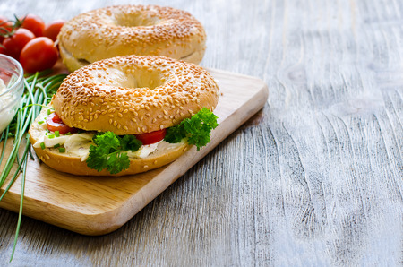 sandwich spread: Bagels sandwiches wtih cream cheese, tomatoes and chives for healthy snack