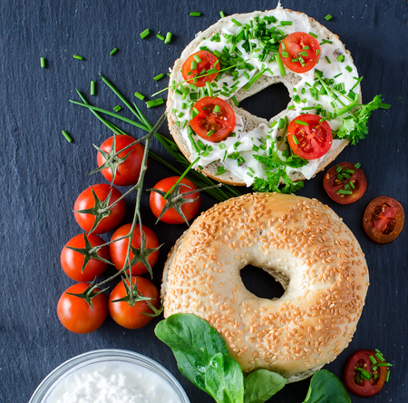Bagels sandwiches with cream cheese, tomatoes and chives for healthy snack Archivio Fotografico